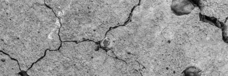 A high resolution old concrete cement with cracks and natural destruction from time and weather conditions. Non-color, monochrome black and white photo.