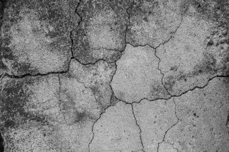 Ein hochauflösender alter Betonzement mit Rissen und natürlicher Zerstörung durch Zeit und Wetterbedingungen. Schwarzweißes Schwarzweißfoto ohne Farbe. Standard-Bild