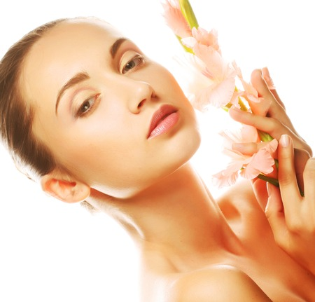fresh face with gladiolus flowers in her hands photo