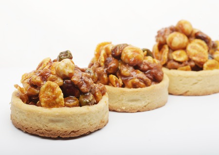 Little nuts tarts. A luscious nutty dessert isolated on white. Stock Photo