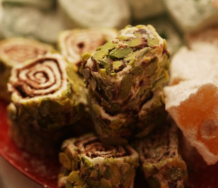 Turkish delight with pistachio nuts over plate photo