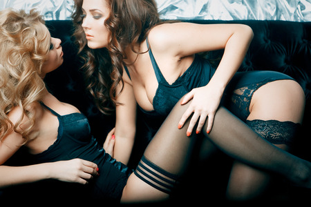 Two beautiful women in lingerie hugging on sofa Stock Photo - 30158846