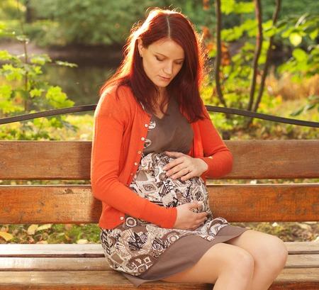 abdomen yellow jacket: beautiful pregnant woman walking in autumn park Stock Photo