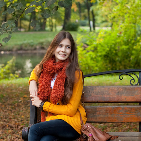 Girl on bench in autumn park photo