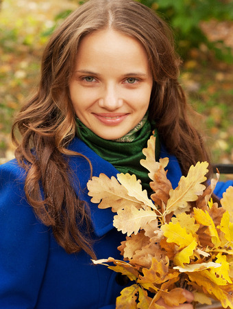 Young  woman with autumn leaves sitting on bench photo