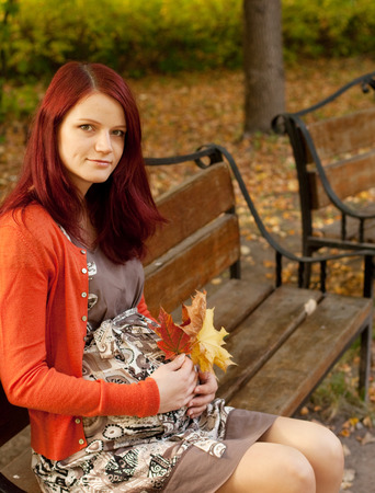 abdomen yellow jacket: beautiful pregnant woman walking in autumn park Stock Photo