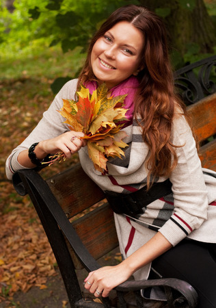 elegant woman with autumn leaves sitting on bench photo