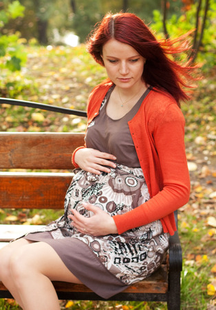 abdomen yellow jacket: pregnant woman walking in autumn park Stock Photo