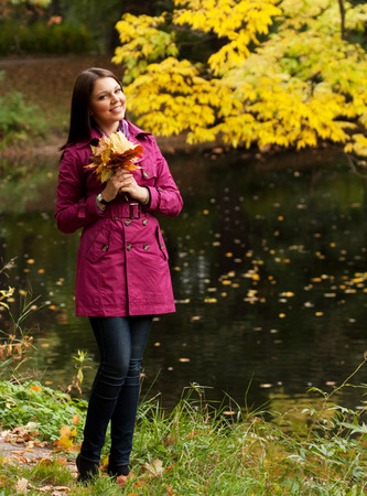 Young woman with autumn leaves in park photo