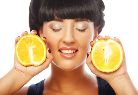 happy girl holding oranges over face photo