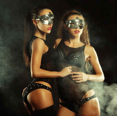 two young sexy striptease dancer with mask photo