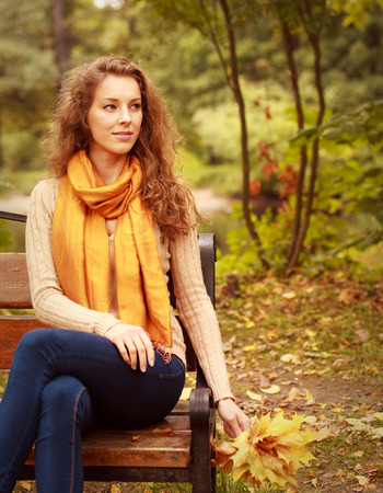 woman with autumn leaves sitting on bench photo