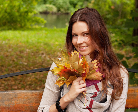 Young elegant woman with autumn leaves photo