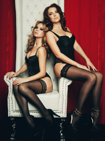 sex pose: two sexy women in lingerie on white throne