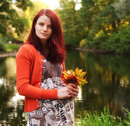 abdomen yellow jacket: pregnant woman walking in autumn park Stock Photo