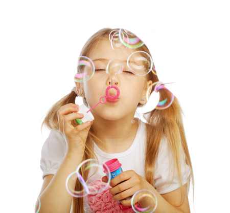 blowing bubbles: funny lovely little girl blowing soap bubbles