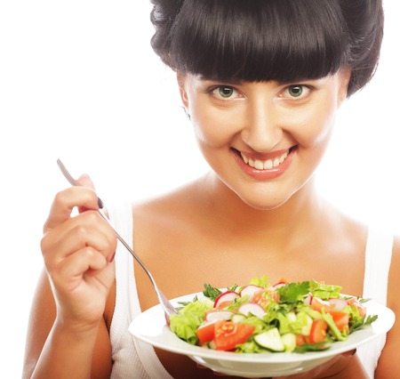 Young happy woman eating salad. photo
