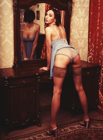 striptease women: sexy brunette posing next to the mirror