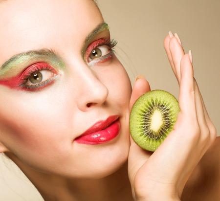 lifestile: woman with bright make up holding kiwi Stock Photo