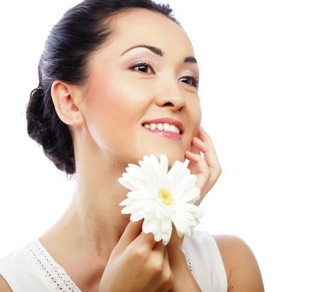 mujer asiática joven que sostiene la flor blanca del gerber