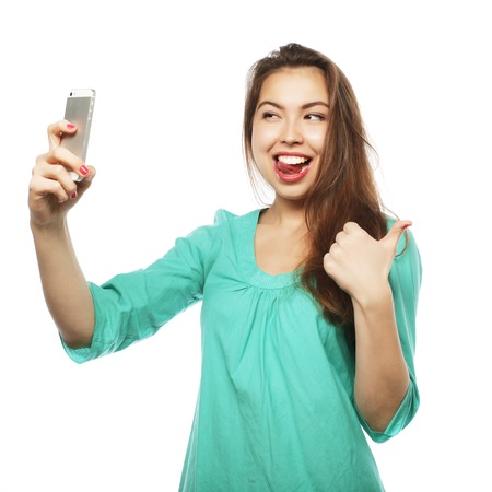 people   lifestyle: People, lifestyle and tehnology concept: pretty teen girl wearing green shirt, taking selfies with her smart phone -  isolated on white