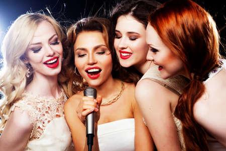 personas cantando: Cuatro hermosas chicas con estilo cantando karaoke en el club Foto de archivo