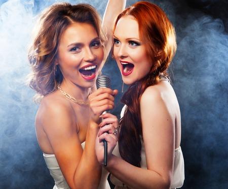 canto: Fiesta de karaoke. Muchachas de la belleza con un micr�fono cantando y bailando sobre fondo oscuro.