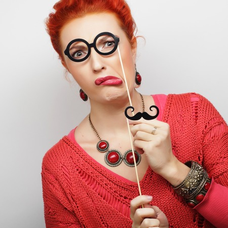 Attractive playful young woman holding mustache and glasses on a stick. Ready for party. Stock Photo