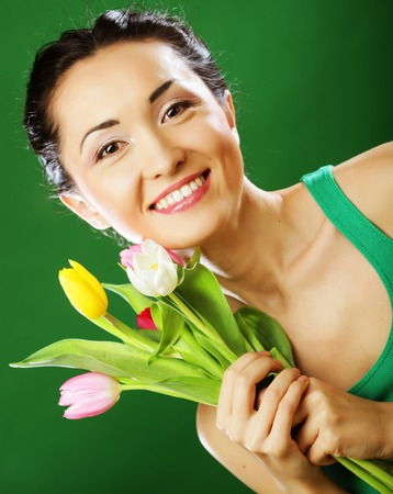 asian tulips: young asian woman holding a bouquet of tulips over green background Stock Photo