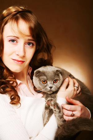 lop eared: Young woman with scottish-fold cat. On brown background.