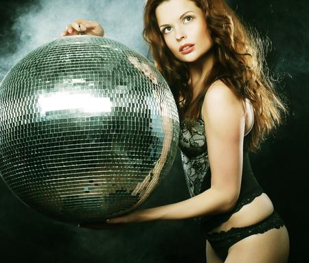 go go dancer: dancer girl in smoke with disco ball over dark background