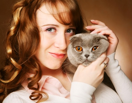 lop eared: Young woman with scottish-fold cat.On brown background.