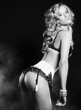 booty: young sexy striptease dancer over dark background Stock Photo