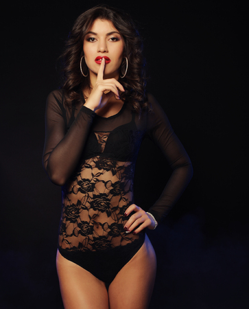 black lingerie: young sexy striptease dancer over dark background Stock Photo