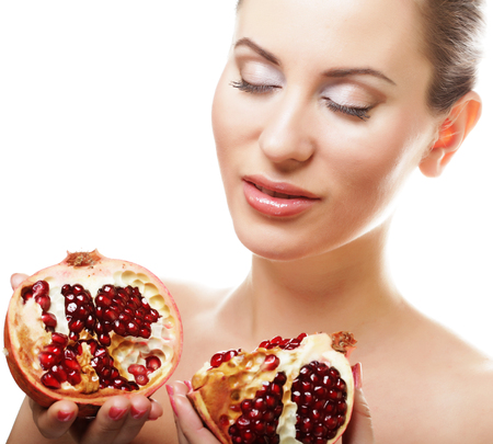 makeup eyes: Portrait of a beautiful young woman with a pomegranate. Isolated on white.