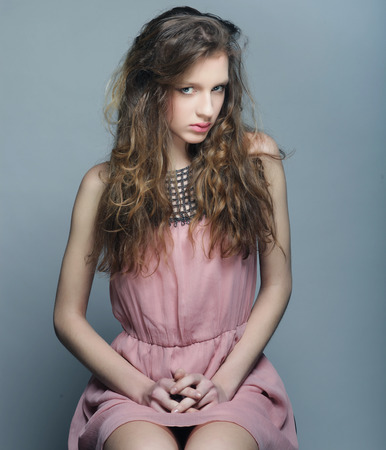 Fashion portrait of beautiful young woman in a summer pink dress.