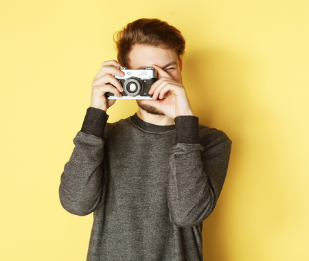 say cheese: Say cheese! Handsome young man looking at camera while standing against yellow background