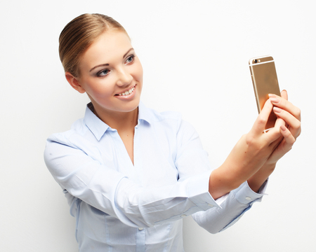 lifestyle, tehnology  and people concept: Beautiful young woman is making selfie photo with smartphone.