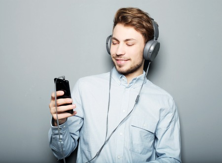expressionless: life style, happiness, emotional and people concept: Man holding mobile phone and lictening to music over grey background
