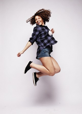 Joyful moments. Full length portrait of a young beautiful e girl wearing a  shorts jumping and smiling  on white background
