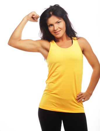 cheerfully: Cheerfully smiling  sporty woman demonstrating biceps, isolated on white background