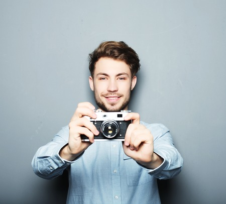 say cheese: Say cheese! Handsome young man looking at camera while standing against grey  background