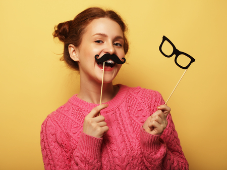mustaches: Young woman with  fake mustaches and glasses over yellow backgro Stock Photo