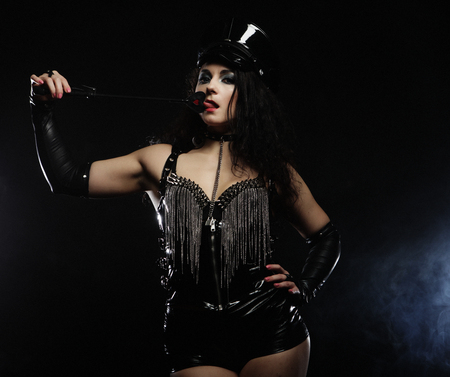 Sexy brunette woman mistress holding whip,over dark backgrouynd