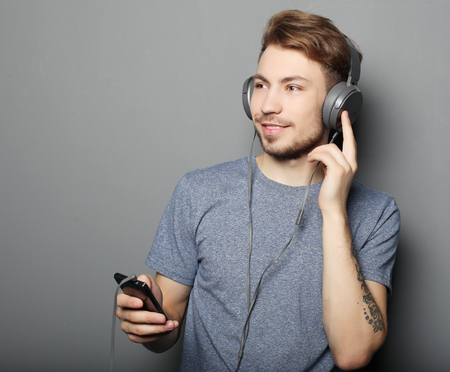 young man wearing headphones and holding mobile phone