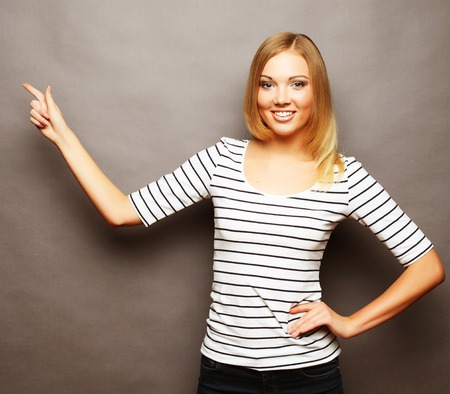 Happy smiling beautiful young woman showing copyspace, visual imaginary or something, or pressing virual button