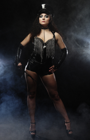 Beautiful mistress dancer in leather shorts and a cap holding a stack and posing over smoke background