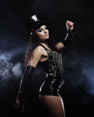 Sexy brünette Frau Herrin hält Peitsche, über dunklem Hintergrund
