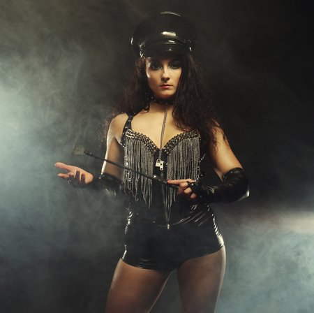 mistress dancer in leather shorts and a cap holding a stack and posing over smoke background, studio shoot.