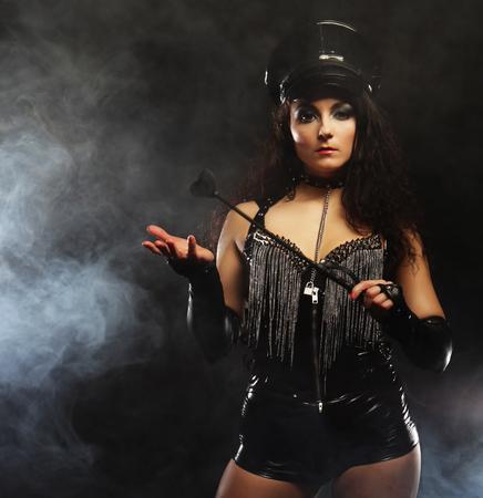 Sexy femme brune maîtresse tenant fouet, sur fond sombre avec de la fumée